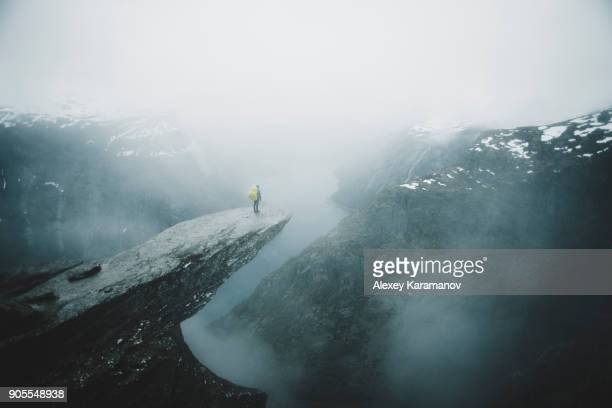 Caucasian man on foggy cliff admiring scenic view of mountain river