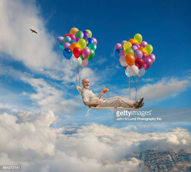 caucasian man on lawn chair floating with balloons in sky - dreamlike stock pictures, royalty-free photos & images