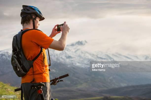 Caucasian man on mountain bike photographing scenic view