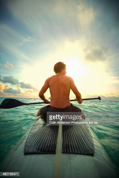 Caucasian man on paddle board in ocean