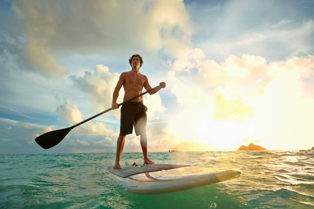 Caucasian Man On Paddle Board In Water Wall Art