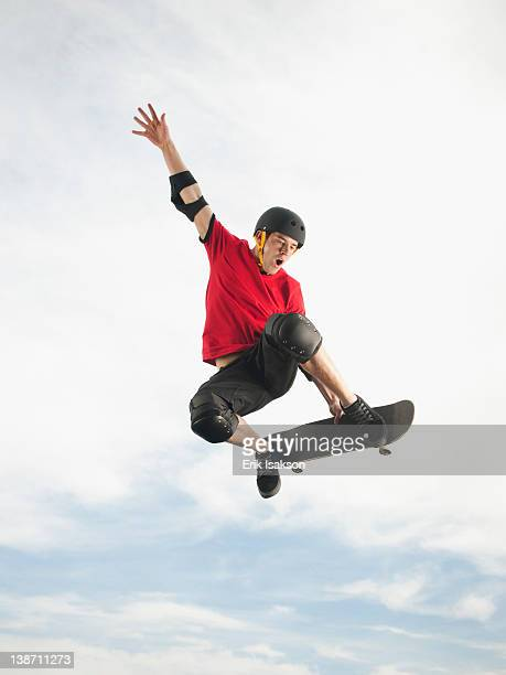 caucasian man on skateboard in mid-air - skating stock pictures, royalty-free photos & images