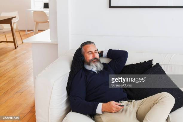 Caucasian man on sofa listening to cell phone with headphones
