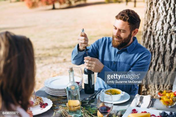 Caucasian man opening wine bottle at outdoor table