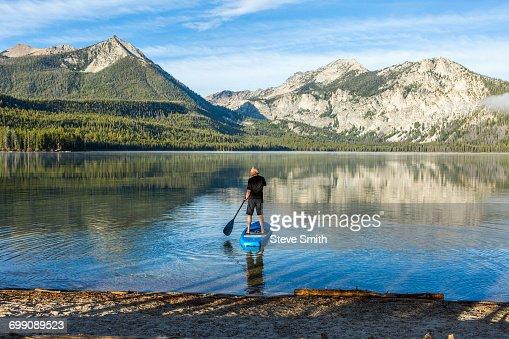 Caucasian man paddleboarding on mountain lake