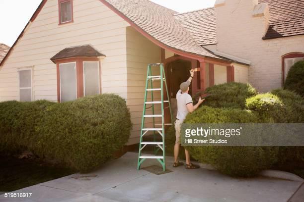 Caucasian man painting edge of house