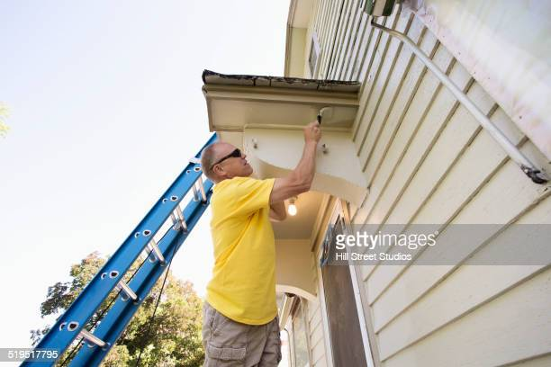 Caucasian man painting edge of house