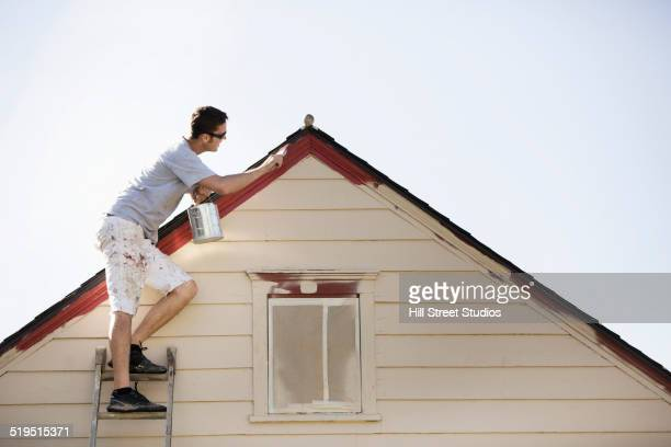 Caucasian man painting edge of roof