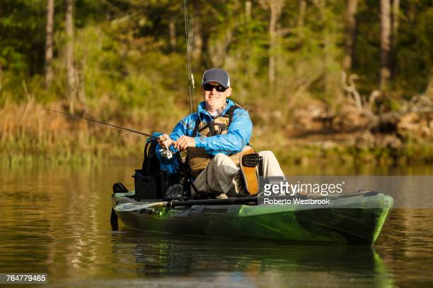 caucasian man pedaling in kayak and fishing - virginia beach stock photos and pictures
