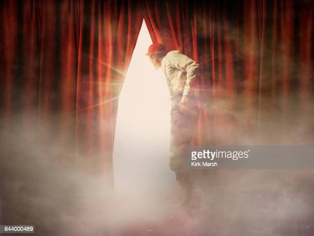 Caucasian man peering through red curtain