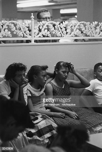 Caucasian man peers over a railing to watch AfricanAmerican protesters during their sitin at Brown's Basement Luncheonette Oklahoma