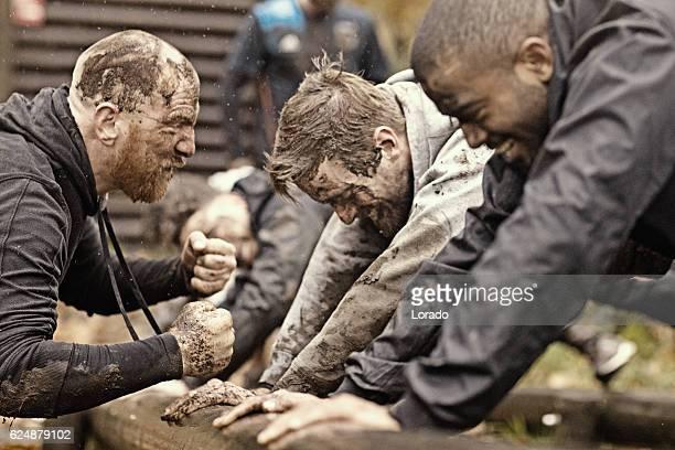 caucasian man personal trainer coaching mud run team of men - tegenspoed stockfoto's en -beelden