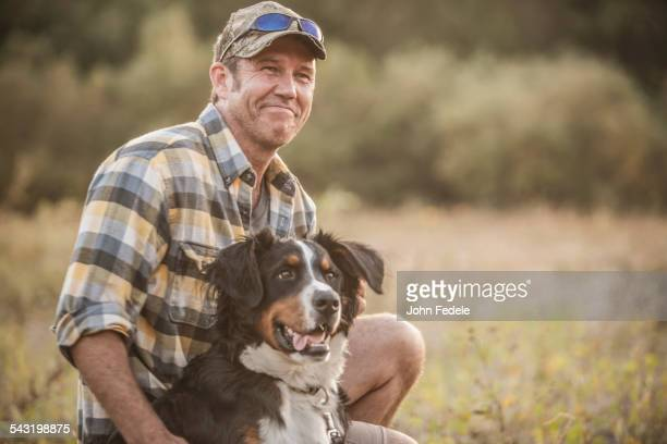 Caucasian man petting dog in rural field
