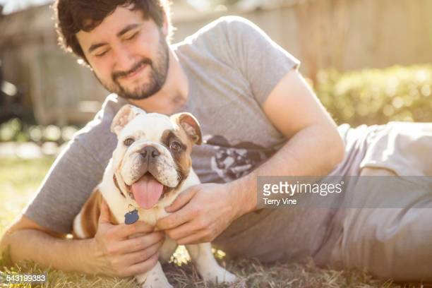 Caucasian man petting dog on lawn