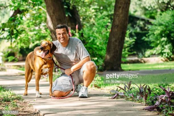 Caucasian man petting dog on sidewalk