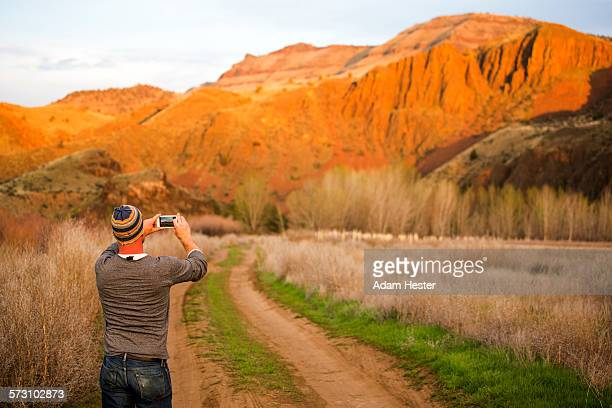 caucasian man photographing desert hills, painted hills, oregon, united states - john day fossil beds national park stock pictures, royalty-free photos & images
