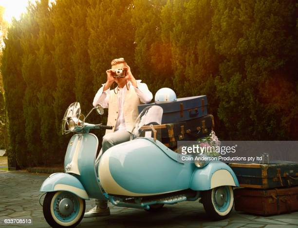 Caucasian man photographing on vintage scooter