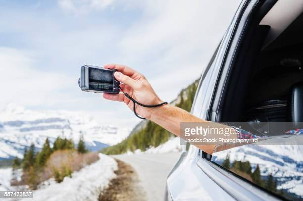 Caucasian man photographing snowy mountain from car window