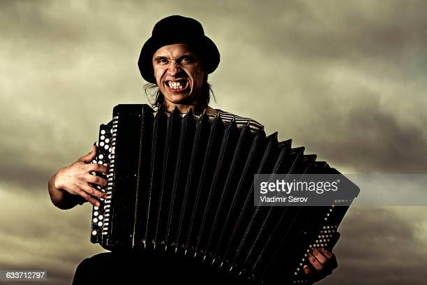 Caucasian man playing accordion outdoors