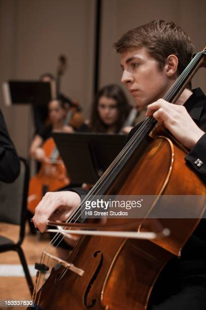 caucasian man playing cello in orchestra - cellist stock pictures, royalty-free photos & images