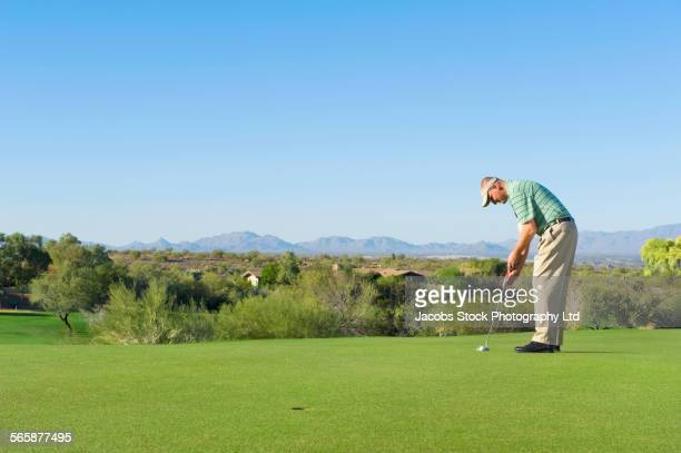 Caucasian man playing golf on golf course