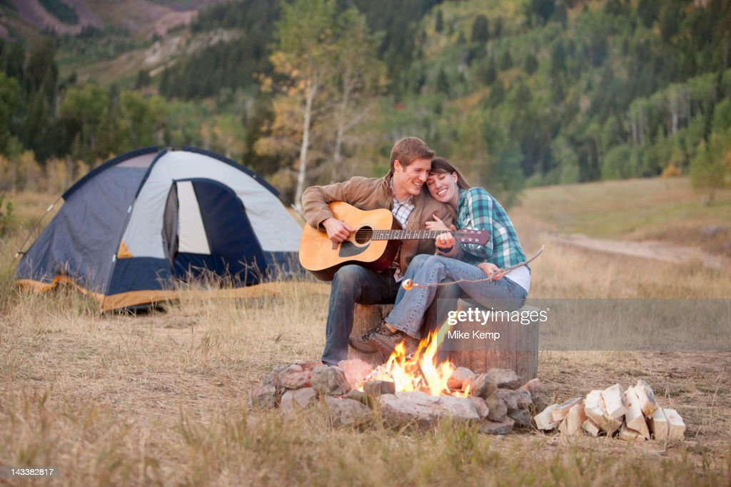 Caucasian man playing guitar for wife near campfire : ストックフォト