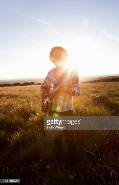 Caucasian man playing guitar in field