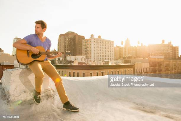 Caucasian man playing guitar on urban rooftop