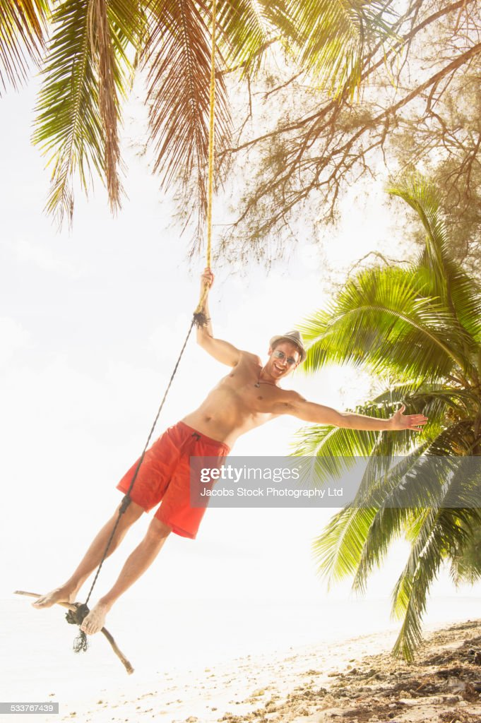 Caucasian man playing on rope swing on tropical beach : Foto stock