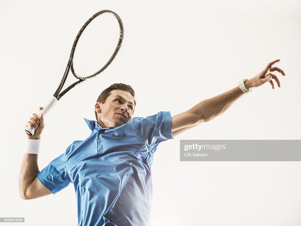 Caucasian man playing tennis : Stock Photo