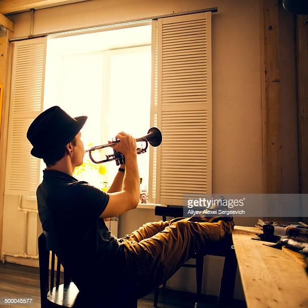 Caucasian man playing trumpet in kitchen