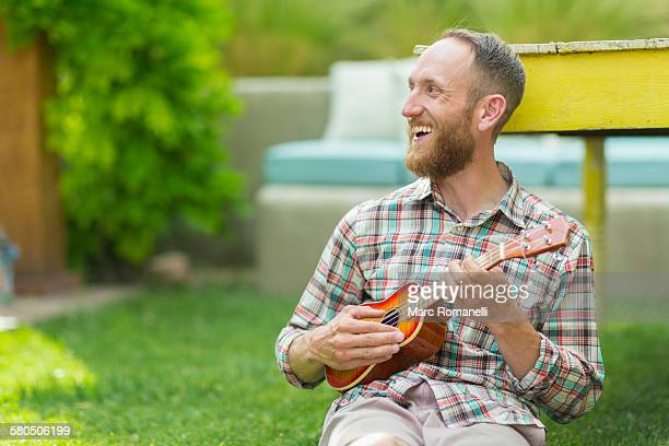 caucasian man playing ukulele in backyard - ukulele stock pictures, royalty-free photos & images
