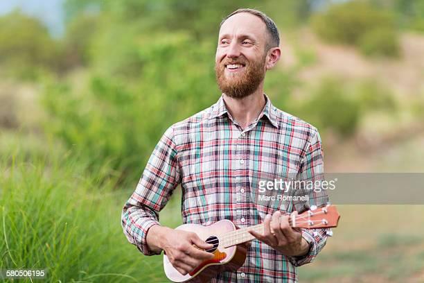 Caucasian man playing ukulele outdoors