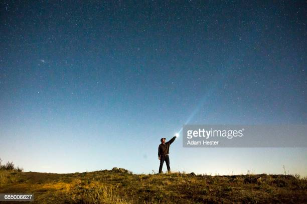 caucasian man pointing flashlight at night sky - flashlight stock pictures, royalty-free photos & images