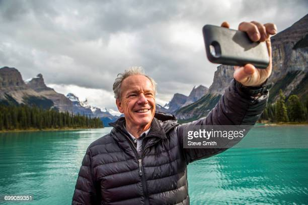 Caucasian man posing for cell phone selfie near mountain lake