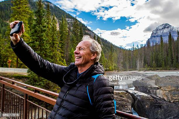 Caucasian man posing for cell phone selfie near mountain