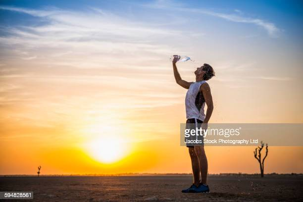 caucasian man pouring water bottle on himself in desert - thirsty stock pictures, royalty-free photos & images