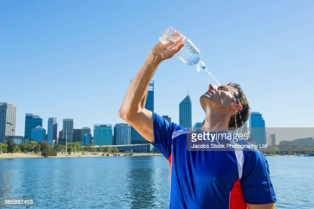 Caucasian man pouring water bottle on his face near Perth city skyline, Western Australia, Australia