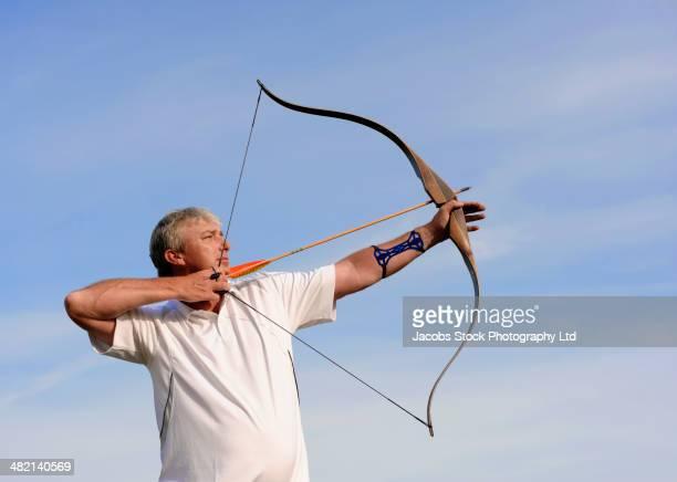 Caucasian man practicing archery outdoors