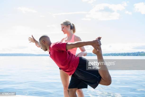 Caucasian man practicing yoga with teacher