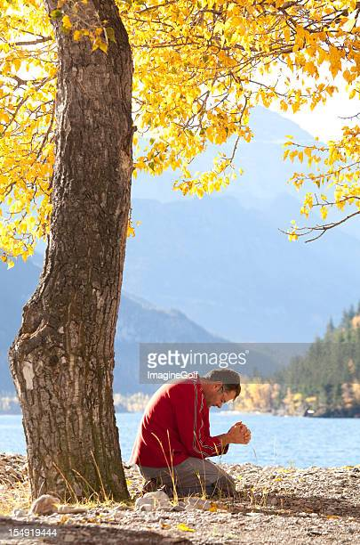 Caucasian Man Praying Beside a Beautiful Mountain Lake