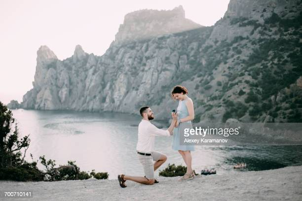 Caucasian man proposing marriage to woman at beach
