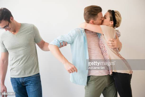 caucasian man pulling arm of friend kissing girlfriend - hot women making out stock pictures, royalty-free photos & images