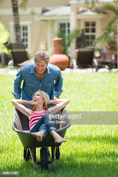 Caucasian man pushing girlfriend in wheelbarrow