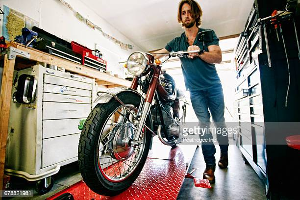 Caucasian man pushing motorcycle on repair stand in garage