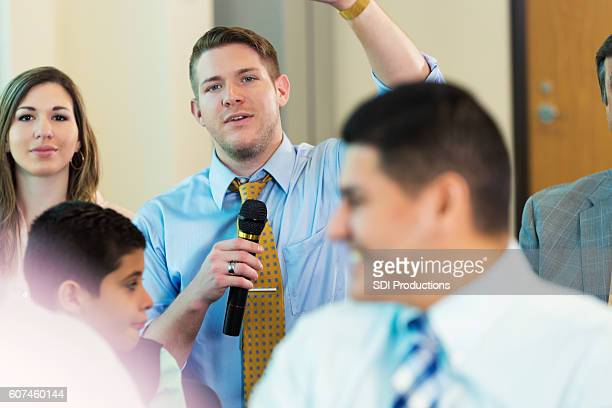 caucasian man raises hand during town hall meeting - town hall meeting stock photos and pictures
