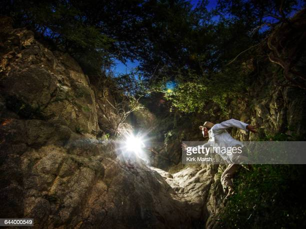 caucasian man reaching for light in forest - grab stock pictures, royalty-free photos & images