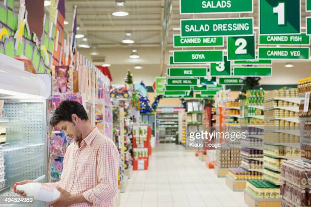 caucasian man reading label in grocery store - milk carton stock photos and pictures