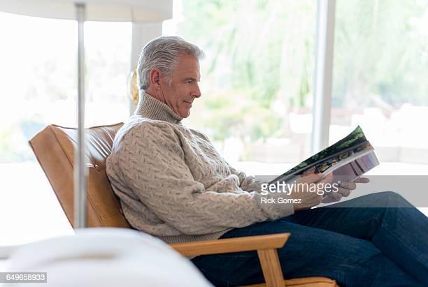 Caucasian man reading magazine in armchair