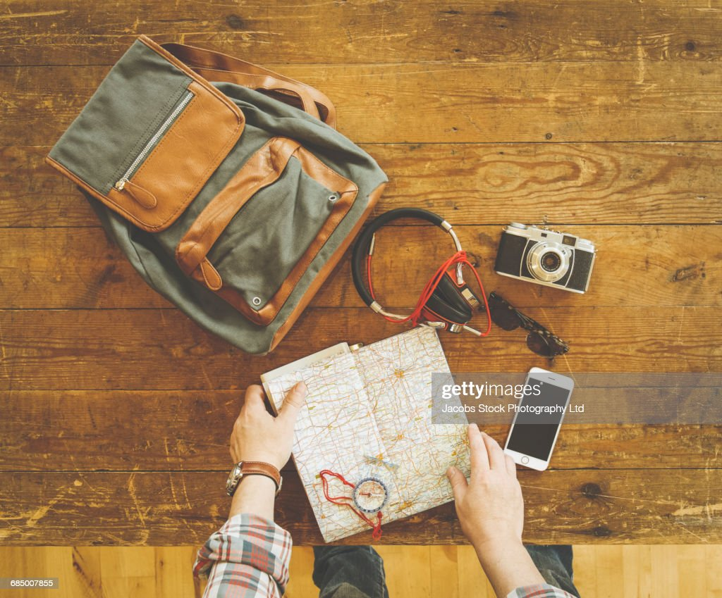 Caucasian man reading map with travel accessories on wooden table : Stock Photo